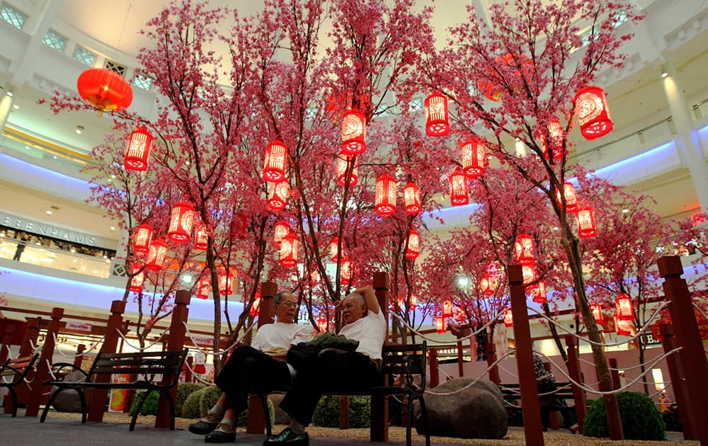 Two shopper resting behind the Chinese plum blossoms trees decoration in Kuala Lumpur, Malaysia. The Lunar New Year begins on Jan. 31 and marks the start of the Year of the Horse, according to the Chinese zodiac.