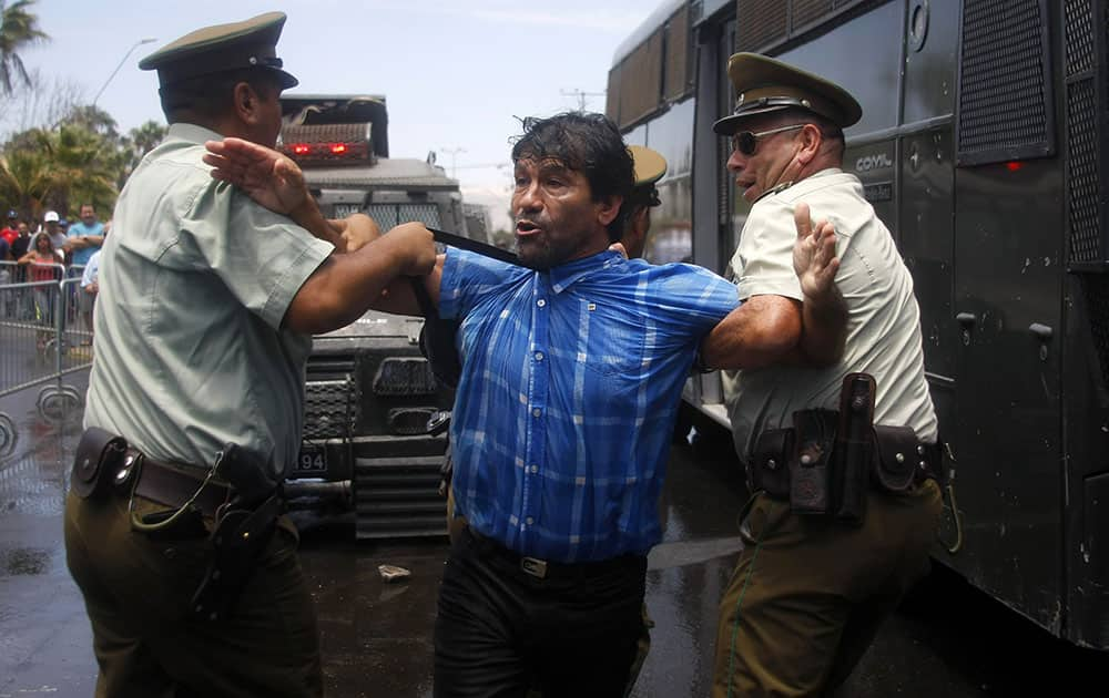 A man protesting the United Nations` highest court ruling on a maritime boundary between Peru and Chile, is detained by police outside a military installation, in Arica, Chile.