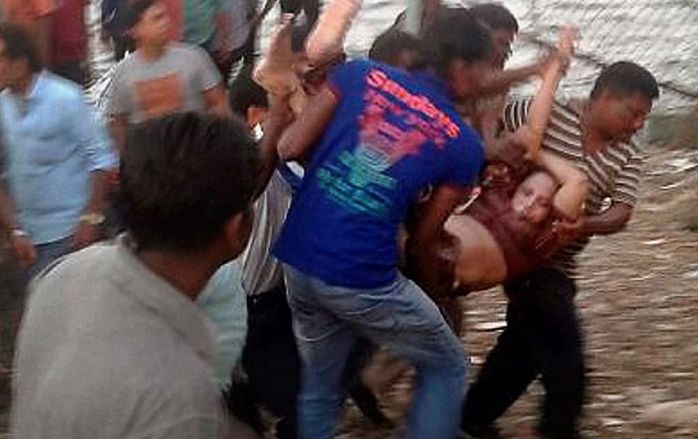 Rescuers carry a woman after a boat capsized off the Andaman and Nicobar islands, India. Police said the tourist boat was overcrowded and may have hit a rock before it went down.