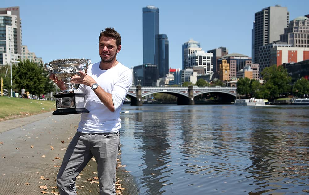 Switzerland`s Stanislas Wawrinka poses with his Australian Open trophy on the banks of the Yarra River following his win over Spain`s Rafael Nadal on Sunday evening in Melbourne.