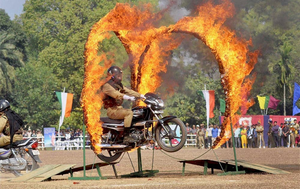 Paramilitary security personnel performs a stunt on a motorcycle during 65th Republic Day parade in Agartala .