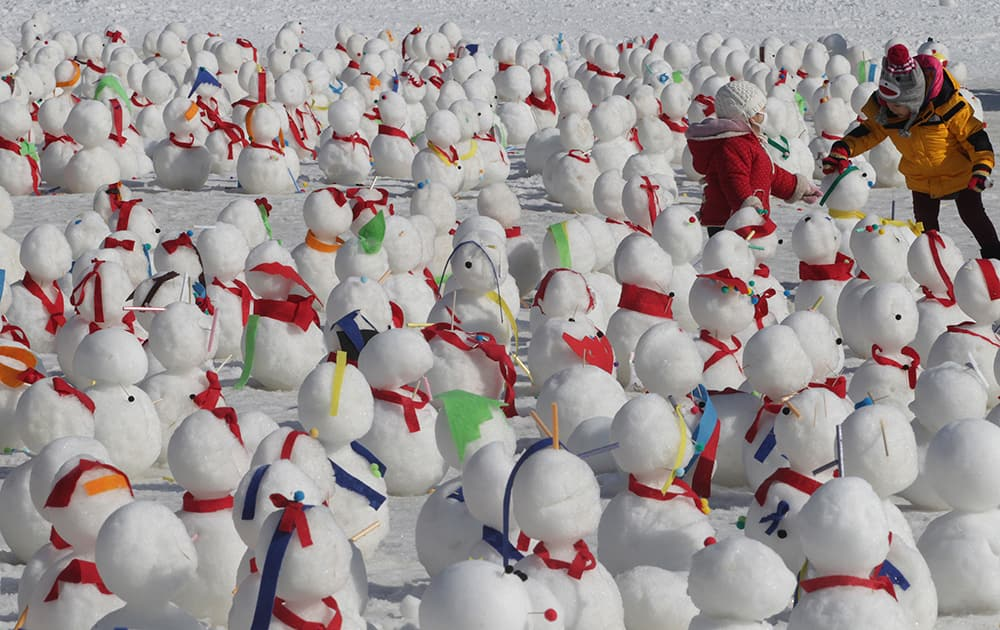 Children play with snowmen on display during an annual Ice Festival in Hwacheon, South Korea.