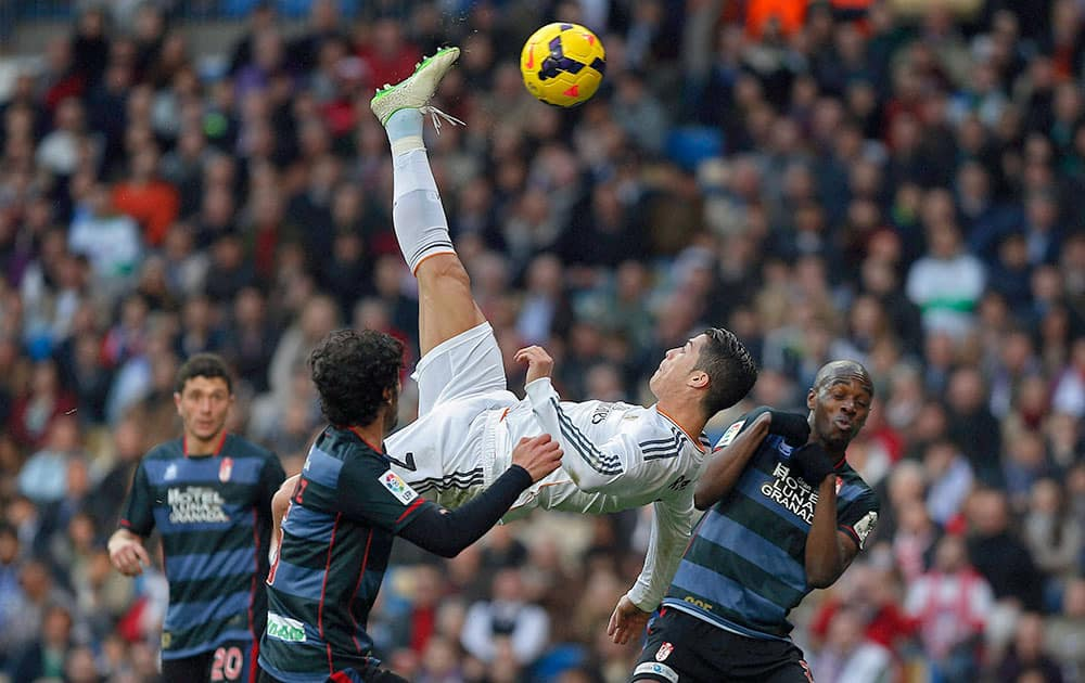 Real Madrid`s Cristiano Ronaldo from Portugal, top, tries to score in between opposition players during a Spanish La Liga soccer match between Real Madrid and Granada at the Santiago Bernabeu stadium in Madrid.