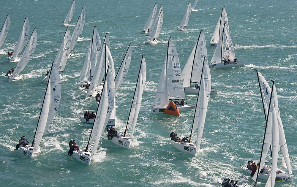 This aerial photo provided by the Florida Keys News Bureau, J/70 boats crowd the windward mark during the final day of racing at the Quantum Key West sailing regatta, in Key West, Fla.