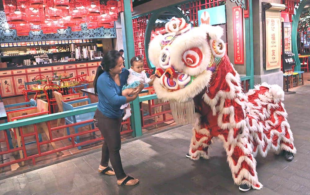 An Indonesian ethnic Chinese with a child watches a dragon dance during Chinese New Year celebrations at a shopping mall in Jakarta.