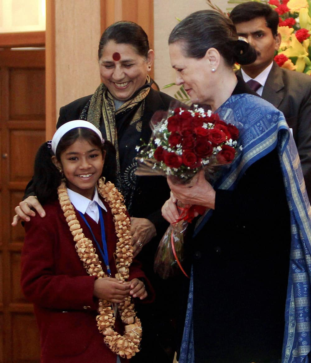 Tanvi Nandkumar Ovhal of Maharashtra presents a bouquet to UPA Chairperson Sonia Gandhi at the National Bravery Awards 2013 function in New Delhi.