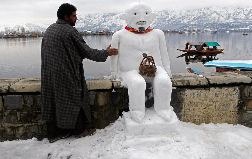 A boatman giving finshing touch to a snow man after heavy snow fall, on banks of Dal Lake in Srinagar.