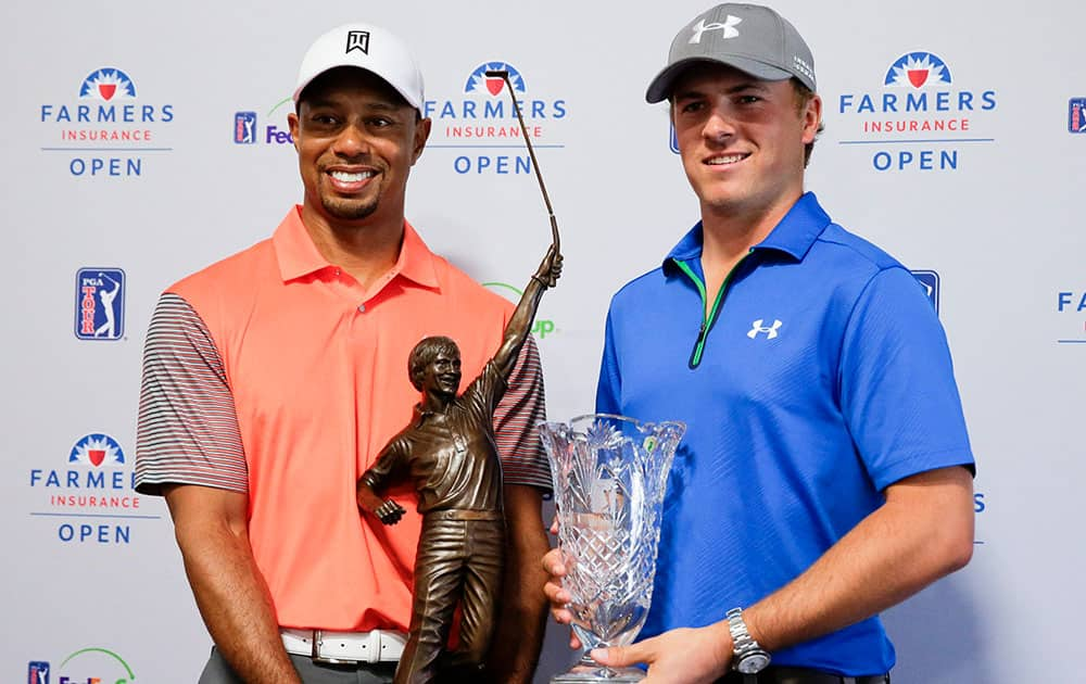 Tiger Woods, 2013 PGA Tour Player of the Year and Jordan Spieth, PGA Tour Rookie of the Year, pose with their trophies during a presentation at a news conference at the Farmers Insurance Open golf tournament at Torrey Pines Golf Course, in San Diego.