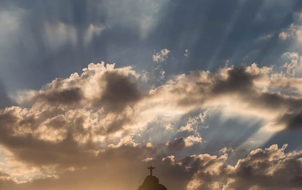 Christ the Redeemer statue is silhouetted against an early evening sky as the sun sets in Rio de Janeiro, Brazil.