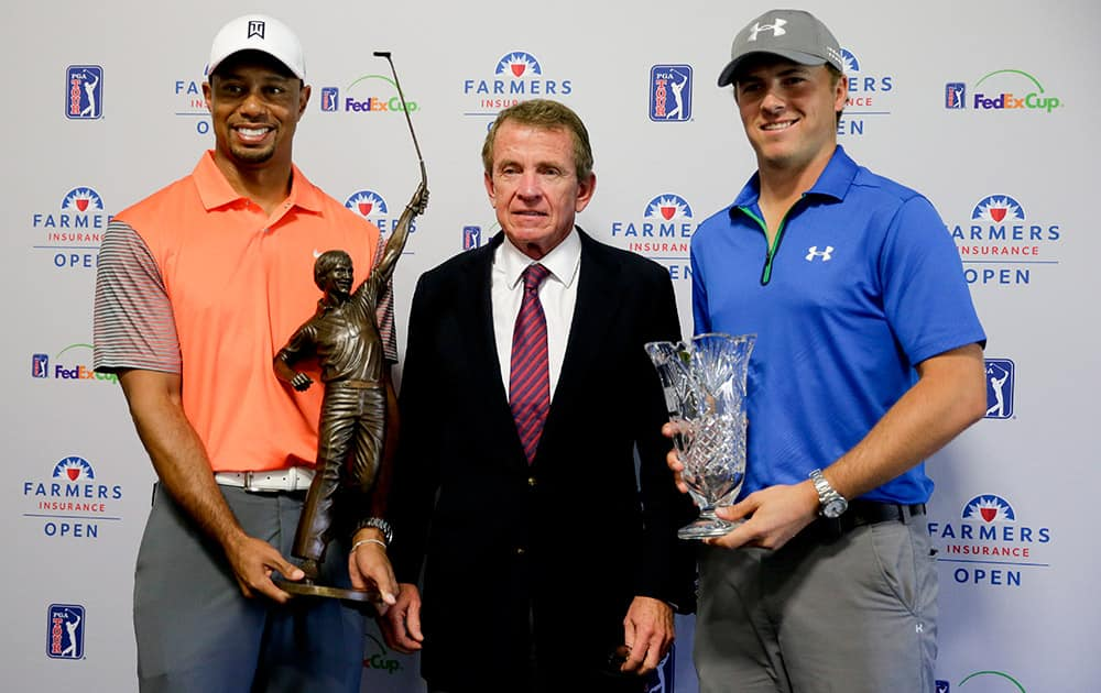 Tiger Woods, left, 2013 PGA Tour Player of the Year, and Jordan Spieth, right, PGA Tour Rookie of the Year, pose with PGA Tour Commissioner Tim Finchem and their trophies during a presentation at the Farmers Insurance Open golf tournament at Torrey Pines Golf Course in San Diego.