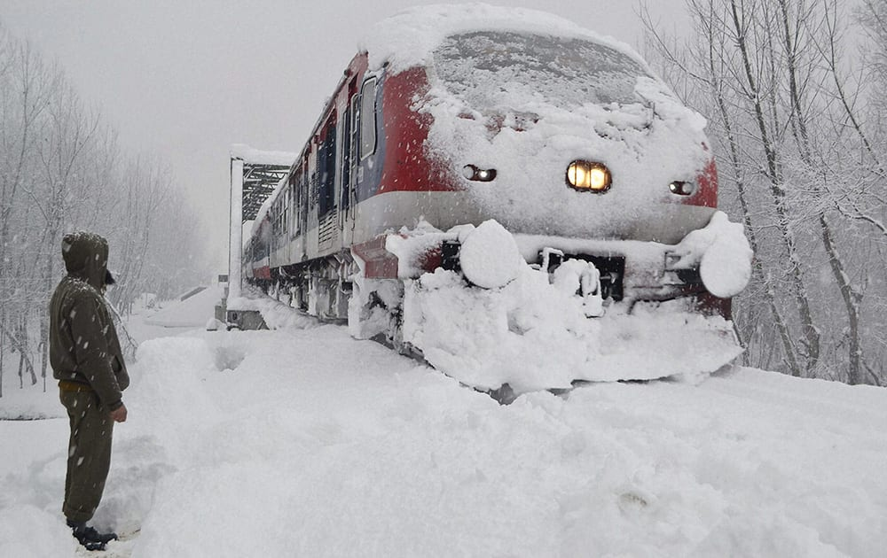 A railway policeman stands guard as a train runs on its tracks amid heavy snowfall in South Kashmir's Anantnag district on Wednesday. Most places in J&K recorded sub-zero temperatures.