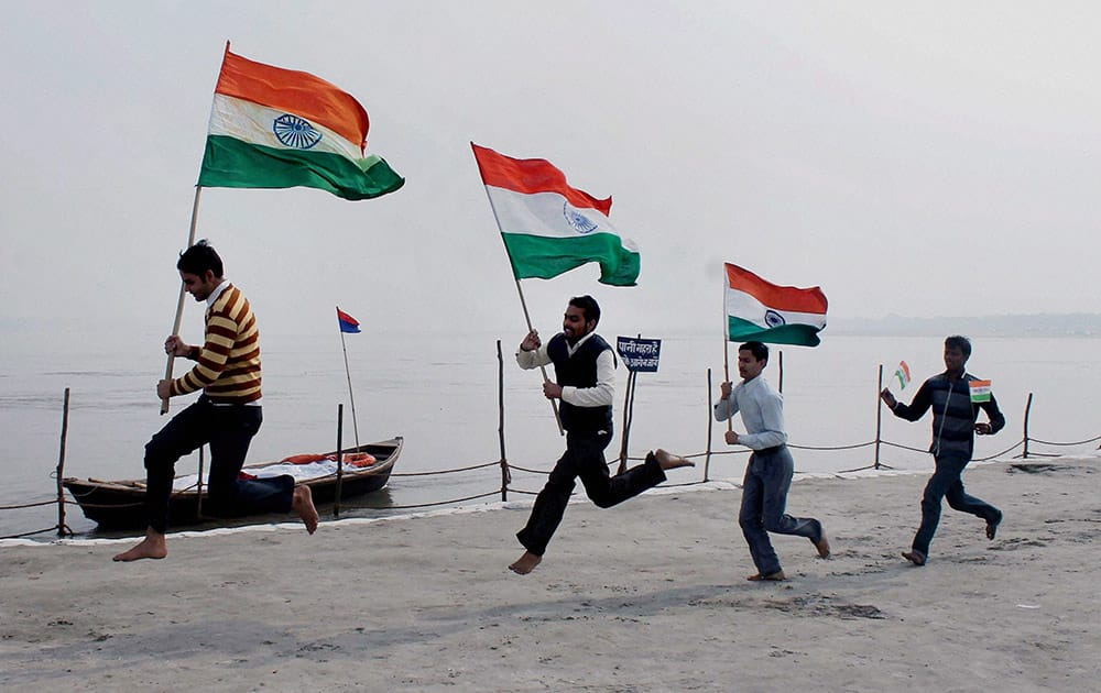 Youths run with Indian National Flags at Sangam ahead of Republic Day celebration in Allahabad.