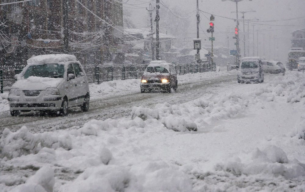 Vehciles move slowly on snow covered road during heavy snowfall in Srinagar.