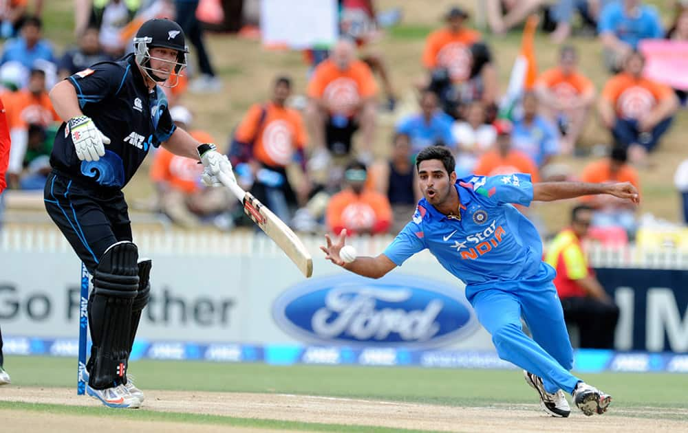 India's Bhuvneshwar Kumar, fields off his own bowling in front New Zealand`s Martin Guptill in the second one-day International cricket match at Seddon Park in Hamilton.