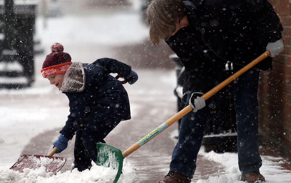 Riley Lopez, 5, left, shovels snow next to his grandmother Bobbie Lopez, right, in downtown Blacksburg, Va.
