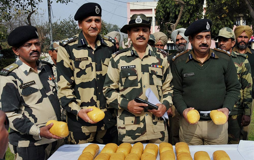 BSF officers and jawans showing 20 kilogram heroin, valued at around Rs 100 crore in international market, recovered after killing of three Pakistani smugglers near Indo Pak international border, about 50 km from Amritsar.
