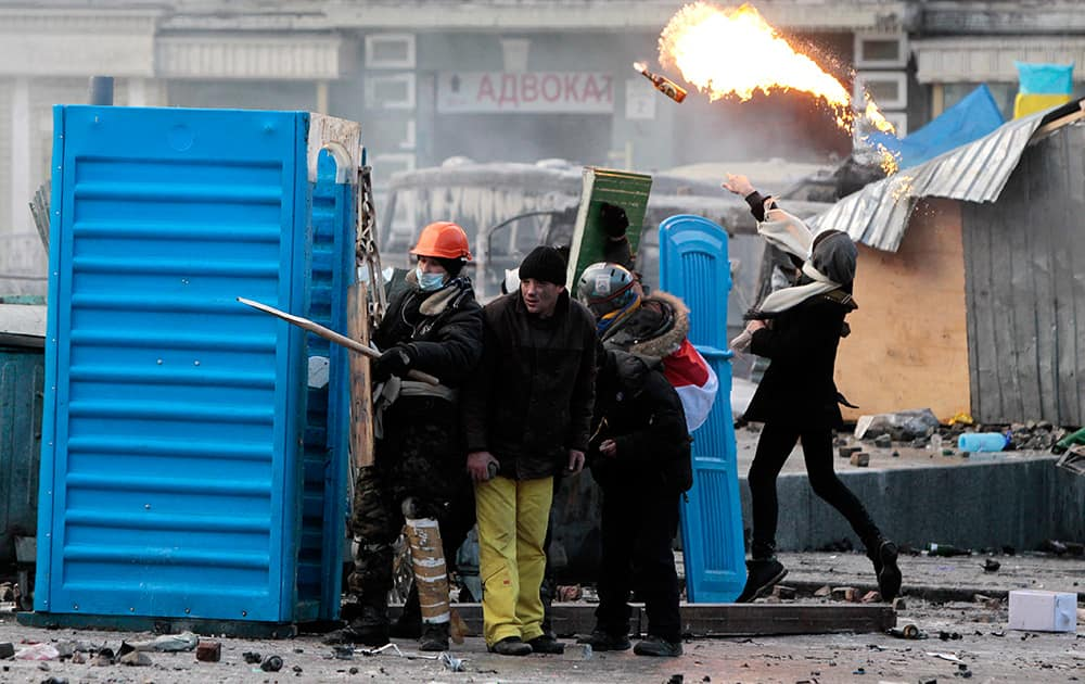 Protesters clash with police, in central Kiev, Ukraine. Protesters erected barricades from charred vehicles and other materials in central Kiev as the sound of stun grenades can be heard in the freezing air as police try to quell anti-government street protests.