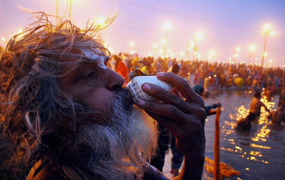 A SADHU BLOWING A CONCH SHELL AFTER TAKING DIP AT SANGAM ON THE OCCASION OF PAUSH PURNIMA IN ALLAHABAD.
