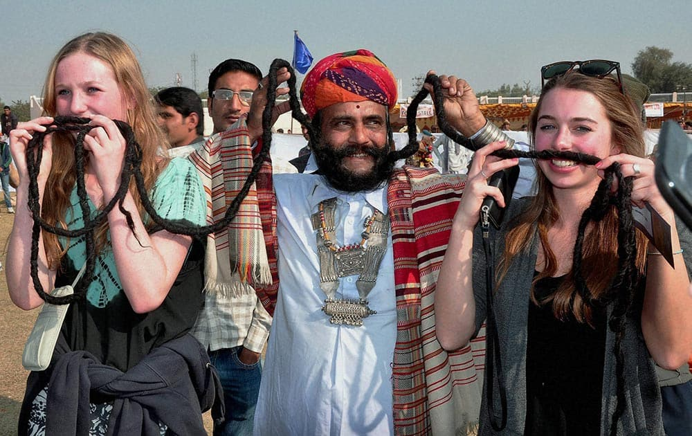 Foreign tourists amuse with the mustache artist during 21st International Camel Festival -2014 in Bikaner.