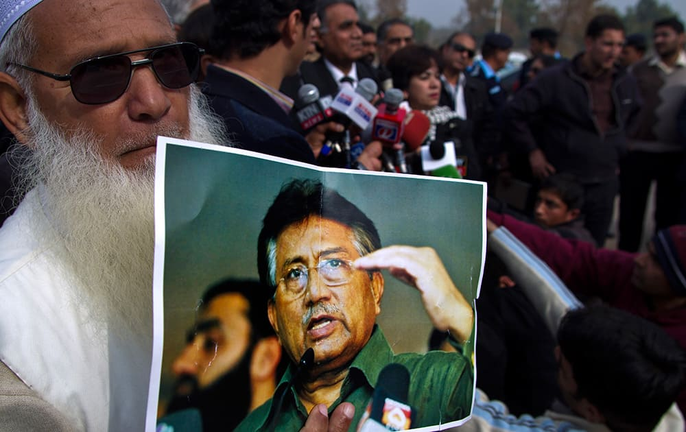A supporter of Pakistan`s former president and military ruler Pervez Musharraf holds a poster with a photo of him during a news conference with Musharraf`s lawyers outside the special court in Islamabad,.