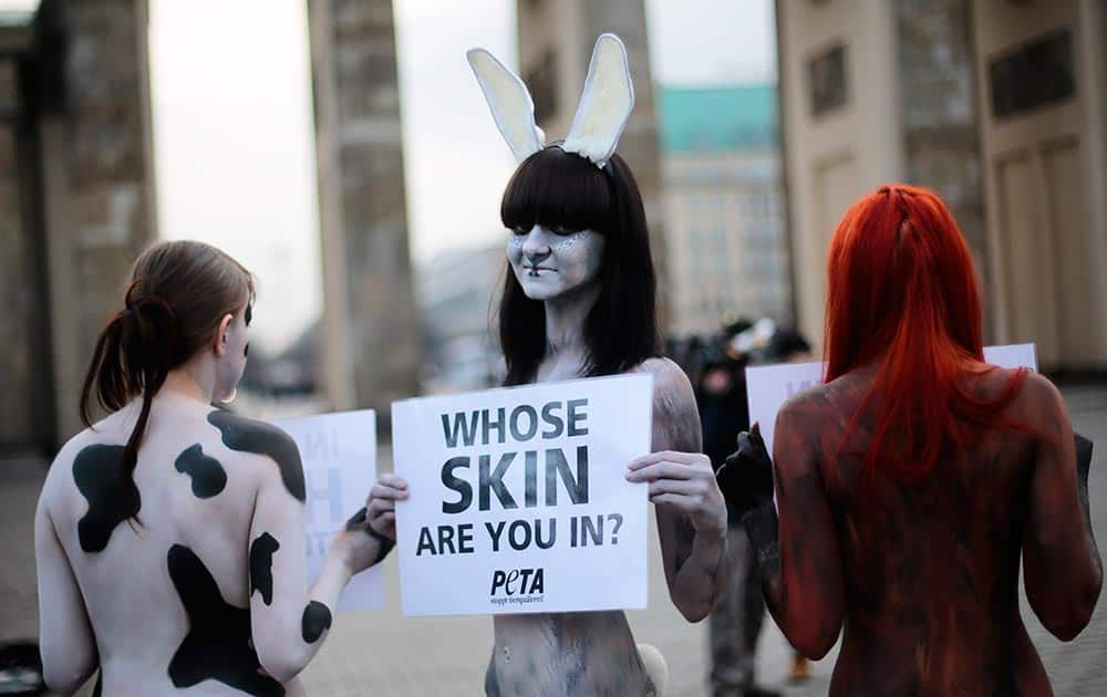 Three protesters of the animal right organization Peta show posters against use of furs in the fashion industry prior to the launch of the Mercedes Benz Fashion Week for Autumn Winter 2014, in Berlin.