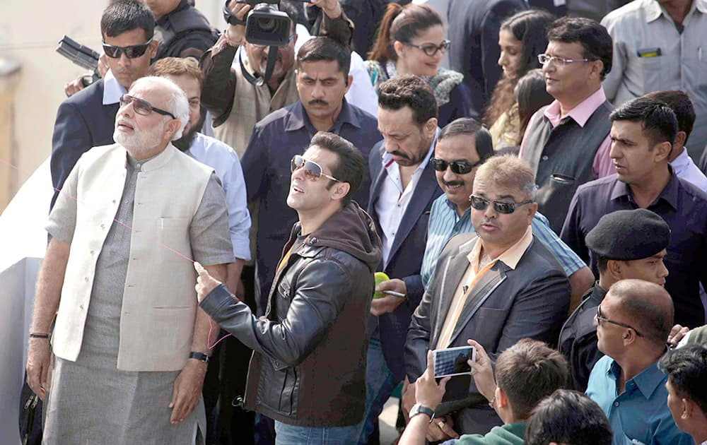 Bollywood actor Salman Khan, flies a kite as Gujarat state Chief Minister Narendra Modi and others watch during the kite festival Uttarayan in Ahmedabad.