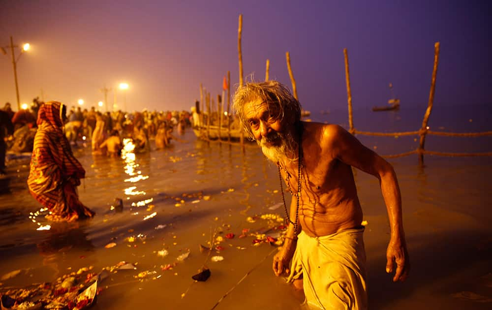 An elderly Hindu devotee reacts to camera after a holy dip at Sangam, the confluence of rivers Ganges and Yamuna on Makar Sankranti festival which also marks the beginning of Magh Mela, in Allahabad.