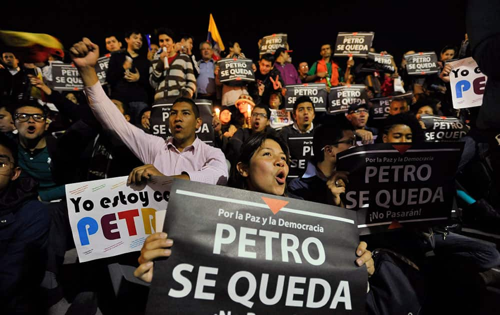 Supporters of Bogota`s Mayor Gustavo Petro hold signs reading in Spanish: `Petro Stays,` in front of the city hall in Bogota, Colombia.