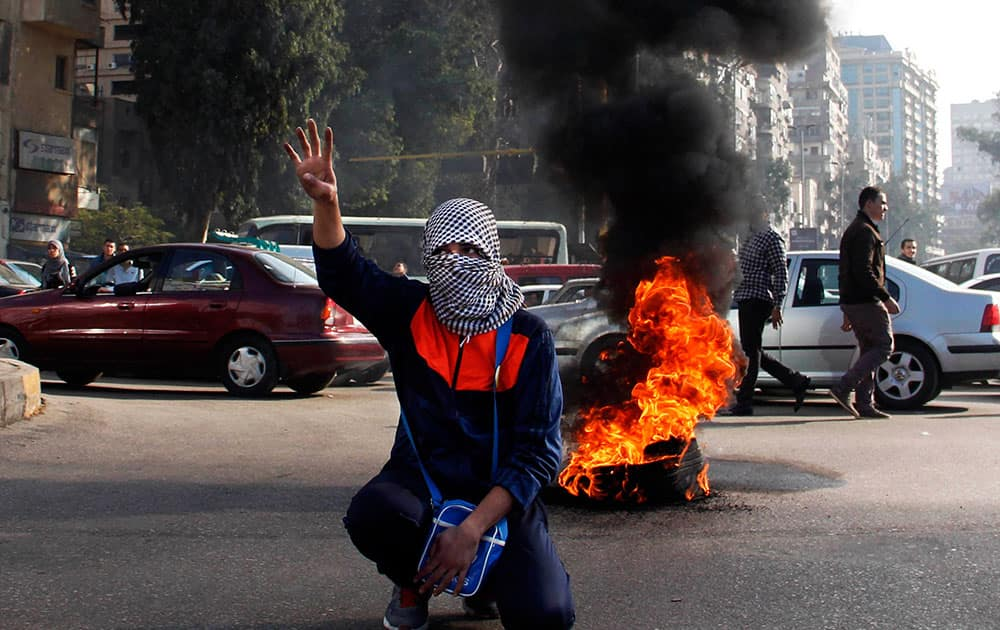 A supporter of ousted leader Mohammed Morsi flashes the `Rabaa` sign during a protest in Nahda Square, near Cairo University in Giza, Egypt.