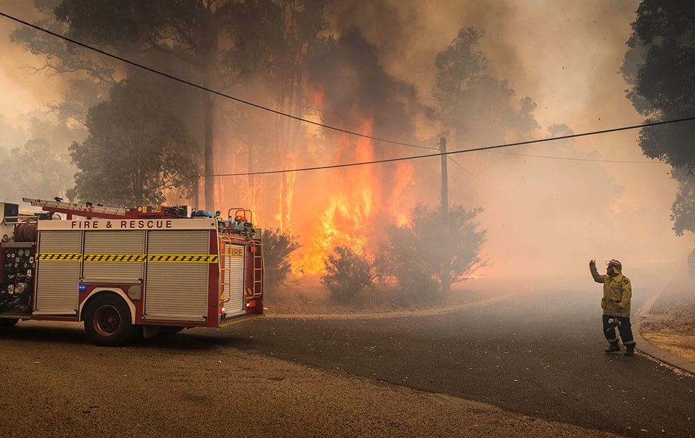 In this image released by the Department of Fire and Emergency Services, a firefighter directs a fire truck in Perth Hills in western Australia.