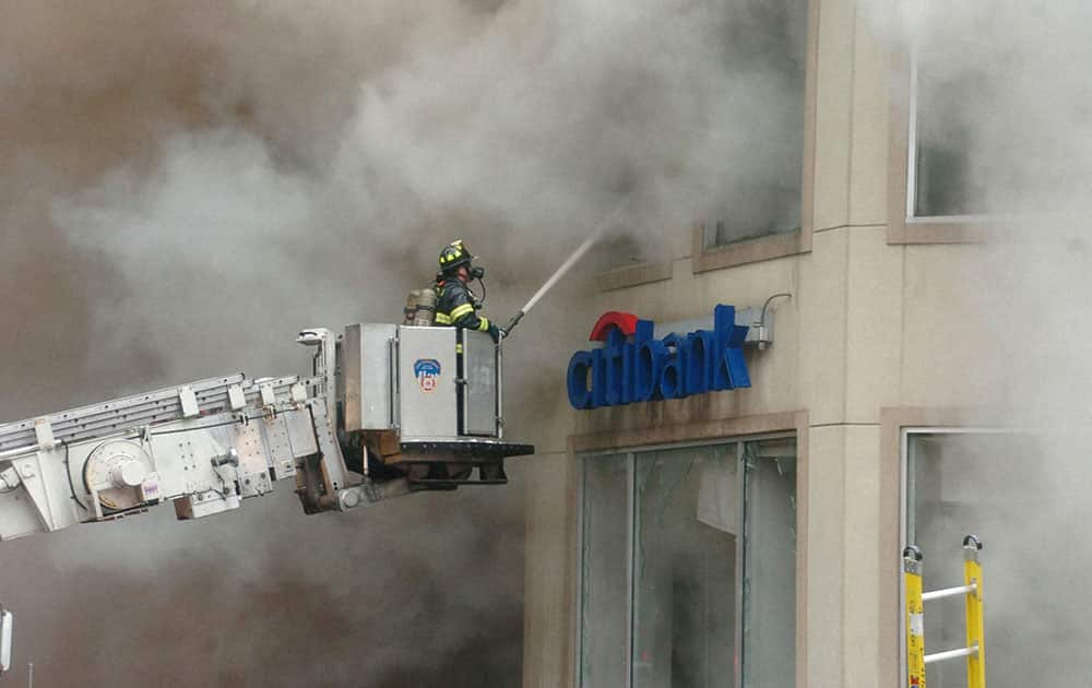 A firefighter from the New York City Fire Department shoots water through second floor window of a Citibank branch as several FDNY companies battle a five alarm fire in the Manhattan borough of New York City.