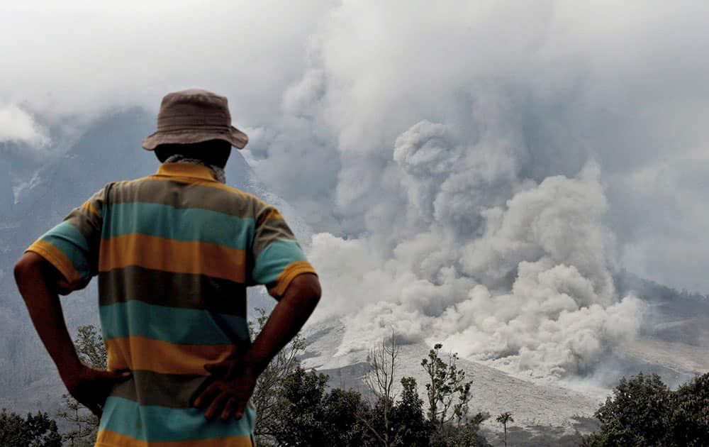 A man watches Mount Sinabung release pyroclastic flows in Berastepu, North Sumatra, Indonesia.