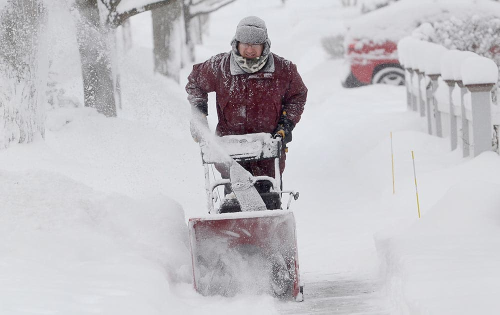 Kevin Pokorny works on his third house clearing snow for neighbors in Barrington, Ill.