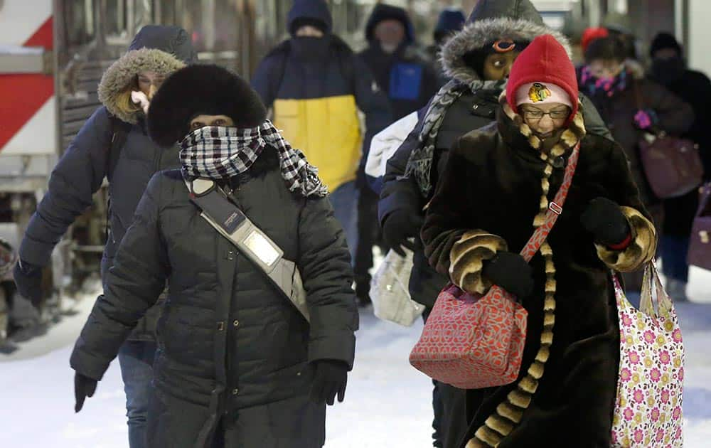 Commuters arrive at the La Salle Street commuter rail station as they experience temperatures well below zero and wind chills expected to reach 40 to 50 below.