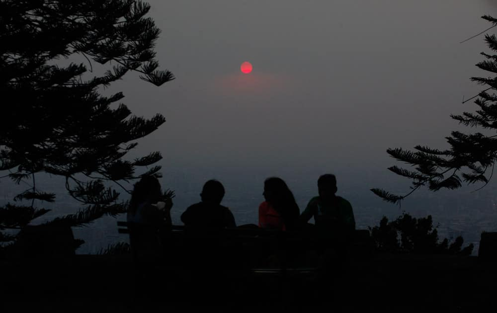 A group of people relax on a park bench at Cerro San Cristobal Park overlooking the Chilean capital which is shrouded by a cloud of smoke from dozens of forest fires that burn near Santiago, Chile.