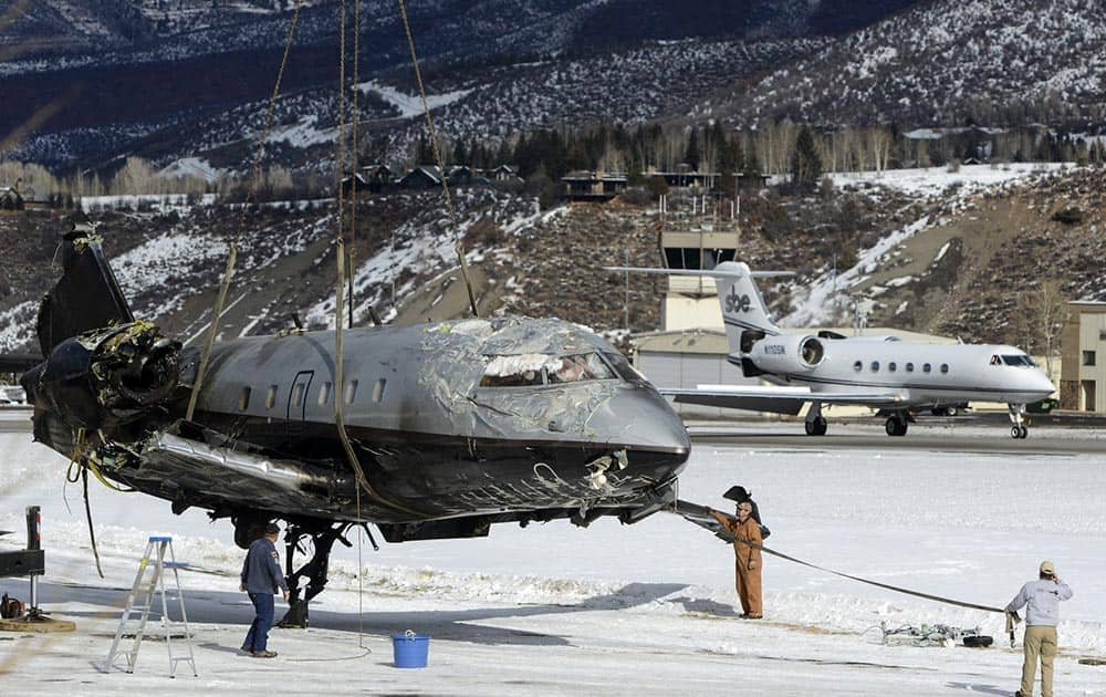 The fuselage of a plane is lifted by crane as the wreckage is removed from a runway, at Aspen-Pitkin County Airport in Aspen, Colo.
