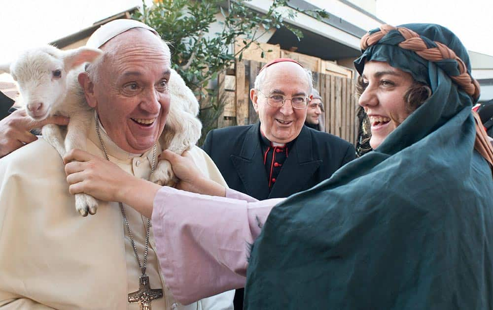 Pope Francis is placed a lamb around his neck as he visits a living nativity scene staged at the St. Alfonso Maria de` Liguori parish church, in the outskirts of Rome.