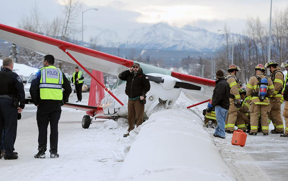 A plane rests in the northbound lane of Boniface Parkway following an emergency landing near Perry Drive south of DeBarr Road  in Anchorage, Alaska.