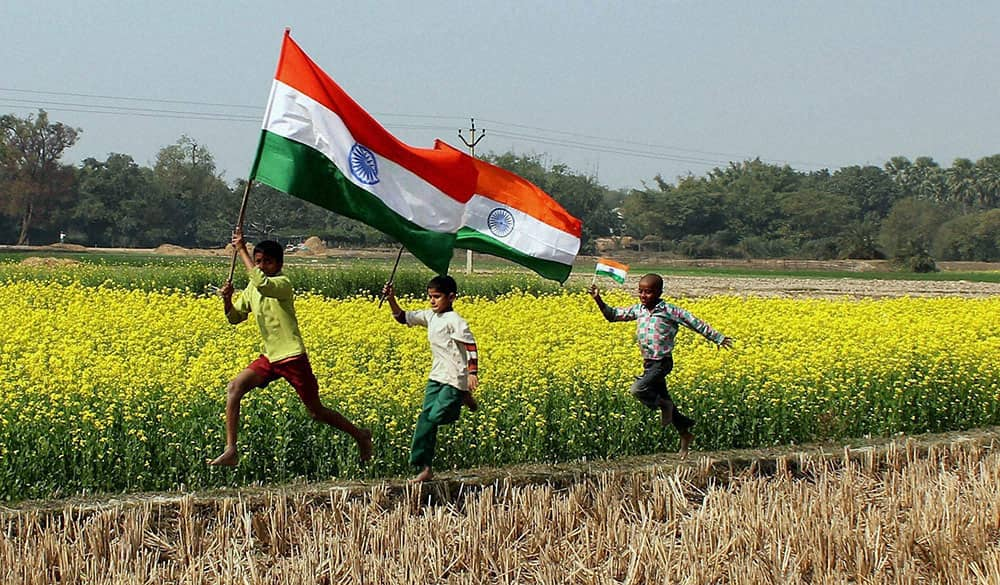 Young boys run with tri-colour flag in the mustard field ahead of Republic Day celebrations at a village near Balurghat in South Dinajpur district of West Bengal.