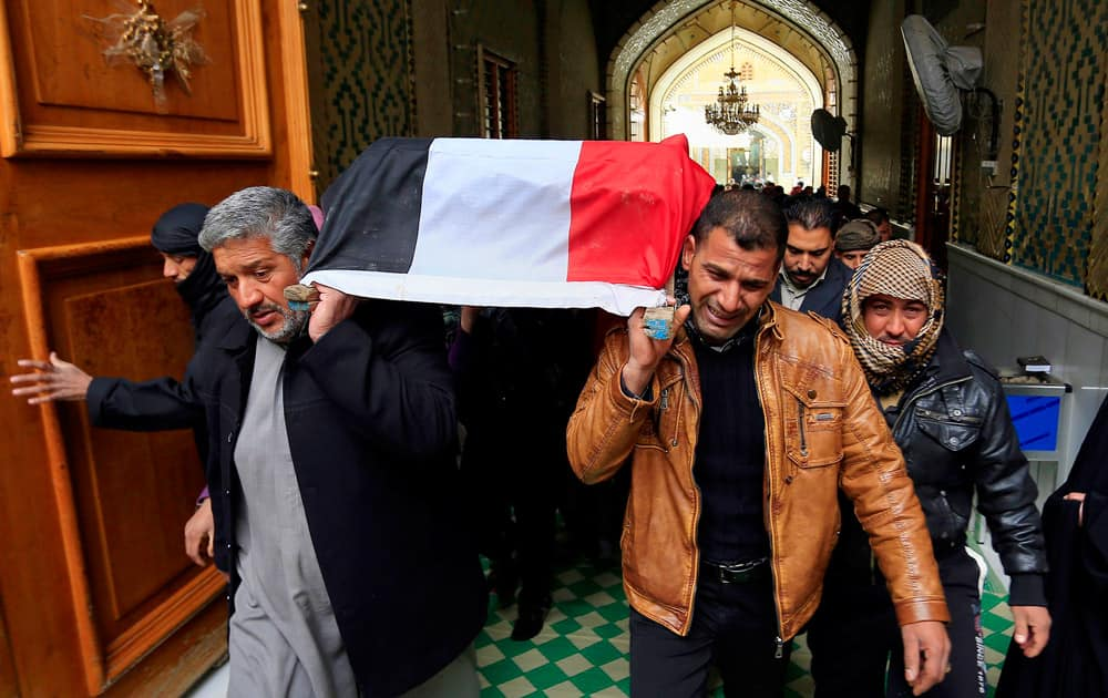 Mourners carry the flag-draped coffin of Iraqi soldier Layth Ahmed, who was killed during clashes in Ramadi, during his funeral procession in the Shiite holy city of Najaf, 100 miles (160 kilometers) south of Baghdad, Iraq.