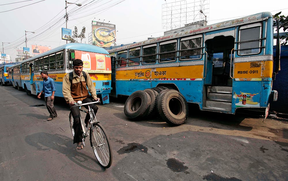 A man rides past parked buses during a 24-hour strike called by private bus transport operators in Kolkata.