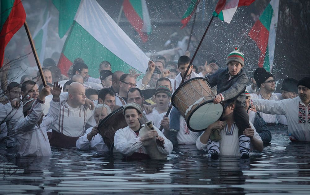 Believers sing and dance in the river Tundzha as they celebrate Epiphany day in the town of Kalofer, Bulgaria.