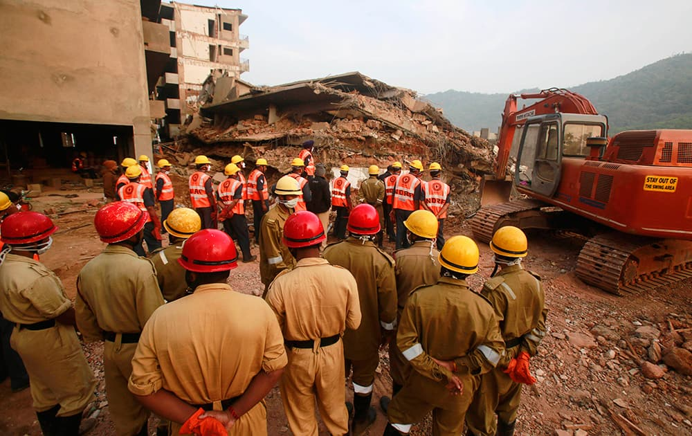 Members of India`s National Disaster Response Force (NDRF) stand watch before their search and rescue operation for survivors in the rubbles of a collapsed building in Canacona, about 70 kilometers (44 miles) from the state capital of Panaji.
