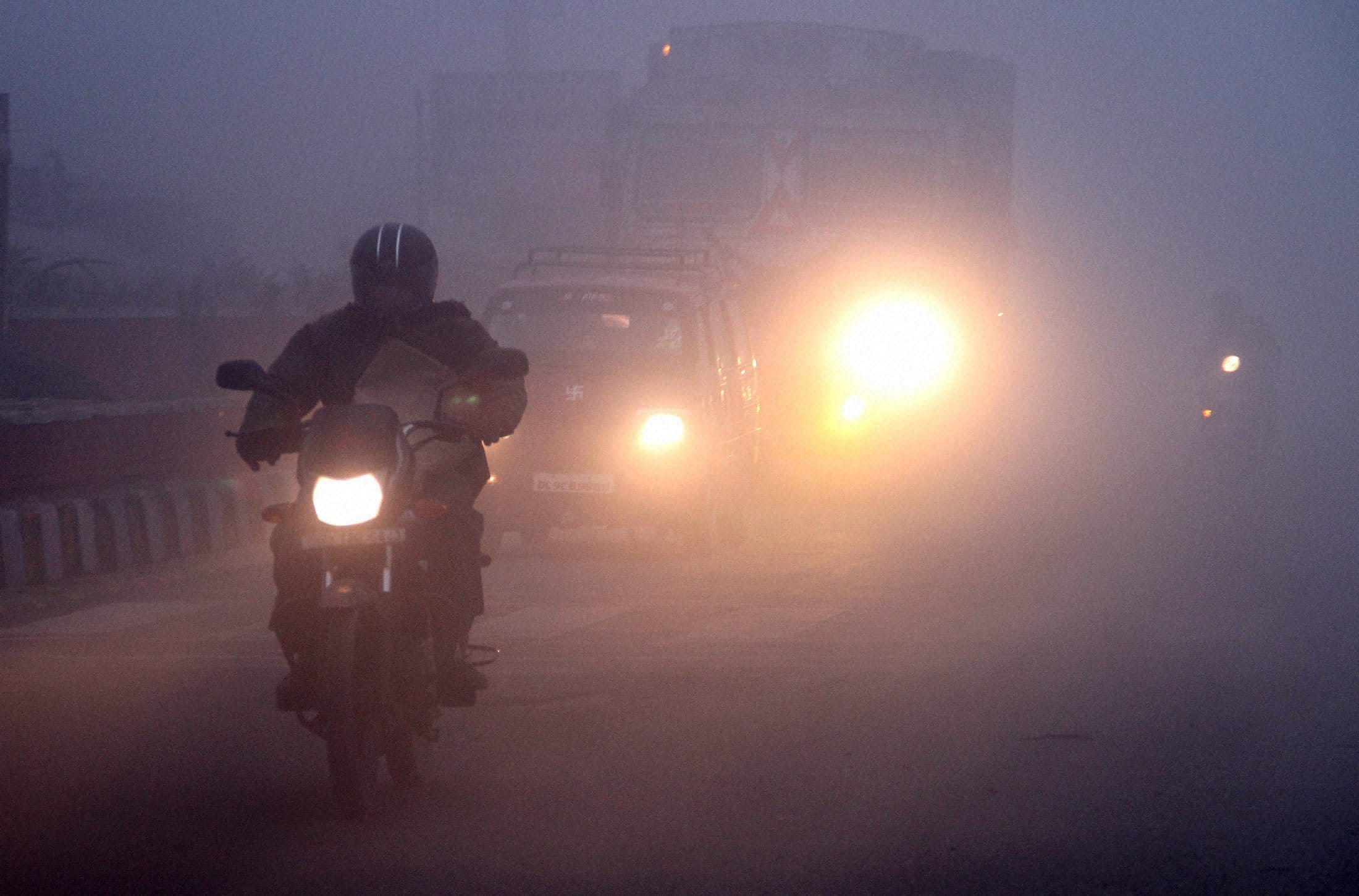 Commuters drive during the foggy morning in New Delhi.