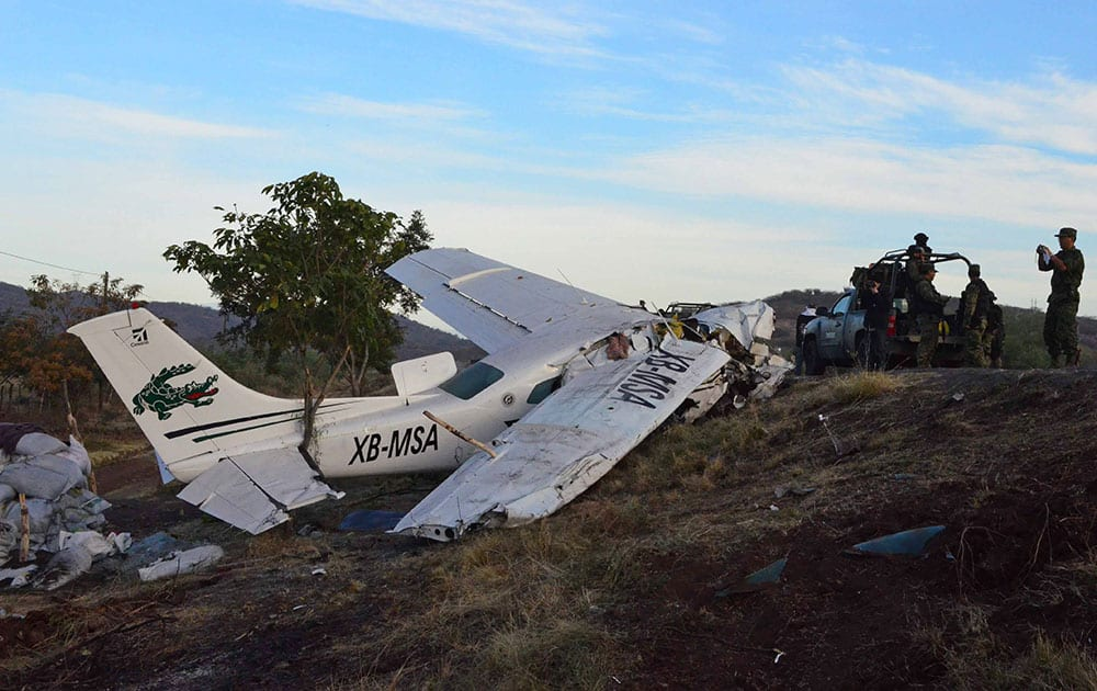 Mexican army soldiers stand next to a single engine aircraft after it crashed near the town of La Huacana, Mexico. The plane crashed in western Mexico, killing one man and injuring four other people, including, Dr. Jose Manuel Mireles, an outspoken doctor who leads a vigilante group, authorities said Sunday.