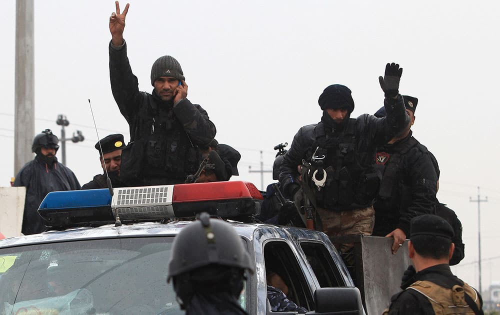An Iraqi riot police officer flashes the V-sign as his unit returns to its headquarters from clashes between Iraqi army and al-Qaeda fighters in Anbar province, in Basra, Iraq`s second-largest city, 550 kilometers (340 miles) southeast of Baghdad.