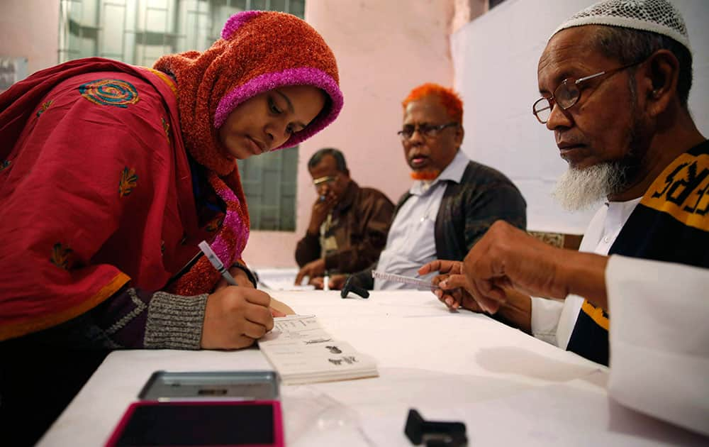 A Bangladeshi woman writes her signature to receive a ballot paper before casting her vote at a polling station in Dhaka, Bangladesh.