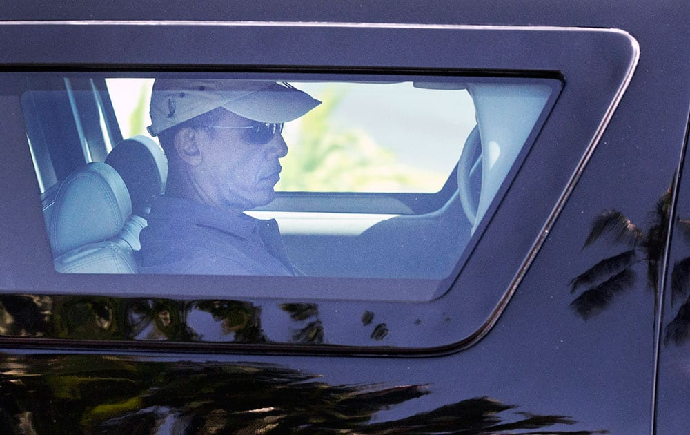 President Barack Obama is seen through the window of his motorcade vehicle as he is driven through the Kailua, Hawaii, neighborhood where he is spending his annual holiday vacation with his family, en route to Marine Corps Base Hawaii, in Kaneohe Bay, Hawaii.