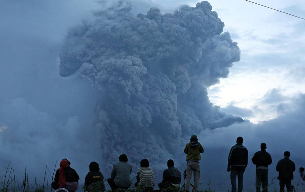 Indonesian men watch Mount Sinabung spewing volcanic materials during an eruption in Tiga Kicat, North Sumatra, Indonesia.