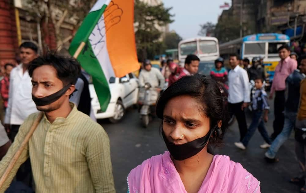 Activists of Indian National Congress with black bands around their mouth block traffic during a protest against a gang-rape and murder of a 16-year-old girl at Madhyamgram, about 25 kilometers (16 miles) north of Kolkata.